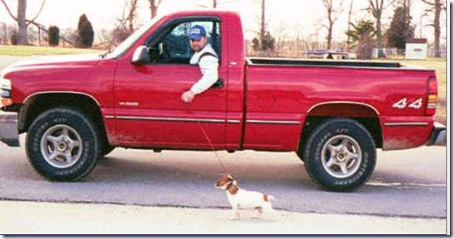 man walking dog in truck